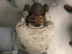 A Marine holds his neck while waiting to take psychological tests at the Marine Corps Air Ground Combat Center in Twentynine Palms, Calif.