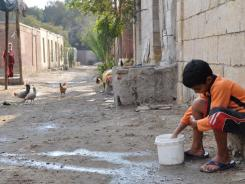 A focus on basic survival:  A boy cleans his hands in Cairo's City of the Dead, not far from Tahrir Square, epicenter of political protests.