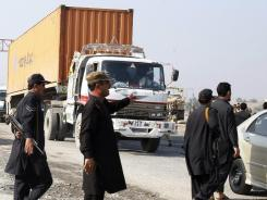 Pakistani security personnel stop trucks with supplies for NATO forces Saturday in Khyber, Pakistan. The trucks were on their way to the Torkham border crossing to enter Afghanistan.