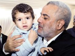Abdelilah Benkirane, the secretary general of Morocco's Islamist Justice and Development Party, poses with his son at the Party headquarters in Rabat, Morocco, on Sunday.