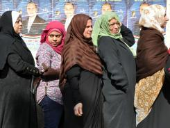Women wait Monday outside a polling station in  Egypt, close to downtown Cairo. Lines were so long that authorities extended the time to vote.