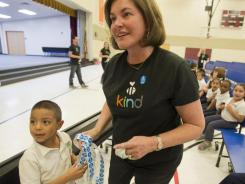 """Marcia Meyer, co-founder of """"The Be Kind People Project,"""" which recognizes teachers, takes help from second grader Adan Marquez at Bernard Black Elementary School in Phoenix on Nov. 10."""