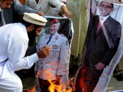 Supporters of Pakistani religious party Jamatud Dawa burn representation of the U. S. flag and posters of President Obama and NATO's general during a rally to condemn NATO strikes on Pakistani posts.