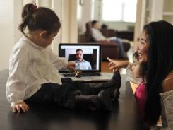 During deployment, Army Major Thomas Murphy, in the background, and his wife, Bianca, right, talked about every other day on Skype. Though the family is reunited, the couple's daughters still enjoy talking to their dad on the computer.