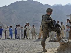 Afghan villagers look on as a U.S. soldier keeps watch during a mission.