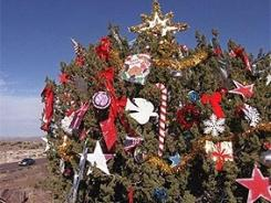 This juniper on Arizona Interstate 17 has been decorated each year for decades. Those responsible for its holiday attire remain a mystery.
