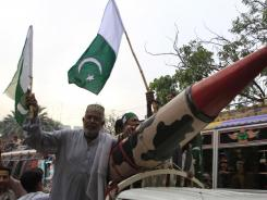 A supporter of Pakistan's ruling People's party stands next to a model of a mock missile at a rally to condemn NATO strikes on Pakistani troops.