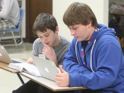 Christian Schaub, left, and Jace Evancho, freshmen at Civic Memorial High School in Bethalto, Ill., do coursework on laptops.