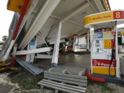 A gas station is left damaged by a tree after Santa Ana winds cause the worst local wind damage in decades Thursday in Pasadena, Calif.