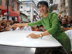 Burma's pro-democracy leader Aung San Suu Kyi shakes hands with supporters Oct. 22 in Rangoon, Burma.