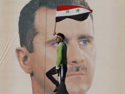 A pro-regime protester waves a national flag in front of Syrian President Bashar Assad's portrait Friday in Damascus, Syria.