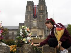 Virginia Tech sophomore Emily Parillo places a flower on a memorial name stone on the Virginia Tech Drillfield in Blacksburg, Va., on Saturday, April 16, 2011.