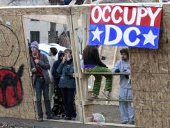 D.C. protesters stand inside a structure set up overnight in McPherson Square on Sunday.