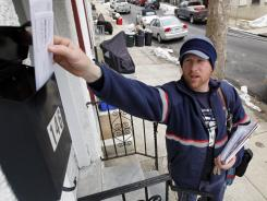 In this March 2, 2010, photo, letter carrier Kevin Pownall delivers mail in Philadelphia.