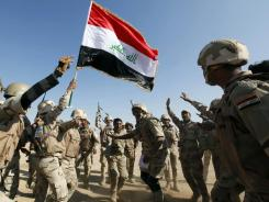 Iraqi army soldiers wave a national flag while celebrating after a live fire exercise Nov. 22 outside Baghdad.