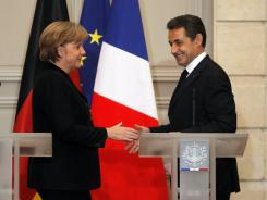 German Chancellor Angela Merkel and France's President Nicolas Sarkozy shake hands after a joint press conference at the Elysee Palace in Paris, Monday.
