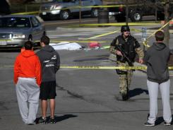 An official secures the scene where a gunman killed a police officer after a traffic stop Thursday on the campus of Virginia Tech, in Blacksburg, Va.