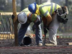 Construction workers check rebar on a highway construction project on Interstate 5 in Los Angeles. Highway workers in some states now qualify for early retirement and higher pensions.
