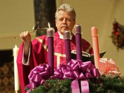 The Rev. Joseph Schlafer lights the first candle in an Advent wreath at St. Joseph Church in Garden City, N.Y.