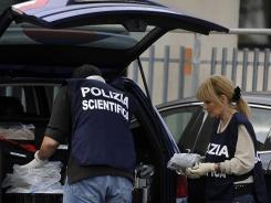 Italian scientific police collect evidence in the parking lot of Equitalia in Rome, after a letter bomb exploded Friday.