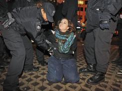 Boston police officers remove an Occupy Boston protester from Dewey Square in Boston before dawn Saturday, Dec. 10.