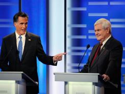 Former Mass. Gov. Mitt Romney points to former speaker of the House Newt Gingrich at the Republican presidential debate Saturday night in Des Moines