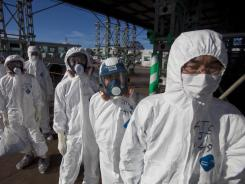 At Fukushima Dai-ichi plant : Workers wait to enter the emergency operation center last month.