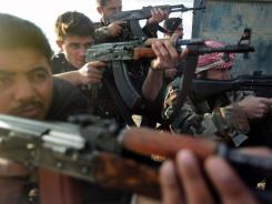 Soldiers of the Free Syrian Army, formed by army deserters, take aim.