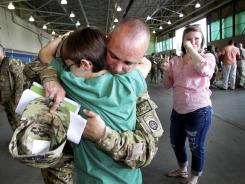 Army 1st Sgt. Jason Friedly of New Bethlehem, Pa., hugs his son Tanner as daughter Lakyn looks on during 82nd Airborne Combat Aviation Brigade deployment to Afghanistan from Fort Bragg, N.C., on Sept. 12.