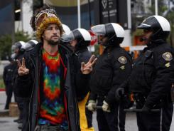 A protester flashes the peace sign to a line of police at the port of Long Beach on Monday.