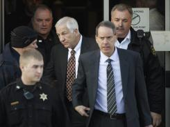 Jerry Sandusky  leaves the Centre County Courthouse with attorney Joe Amendola, second from right on Tuesday.