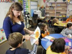 First and second grade teacher Rachel Hine helps her students with a class project on Oct. 31 at De Soto Grade School in De Soto, Ill. Nearly half of America's public schools didn't meet federal achievement standards this year.