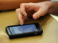 A Franklin High School (Ind.) junior scrolls through Twitter posts on his cellphone. As students gain access to sophisticated electronics, educators are trying to stay on top of cheating trends.
