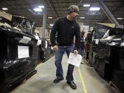 Craig Slack looks over pallets of returned goods before the bidding begins at Overstock.com's warehouse Thursday in Salt Lake City.