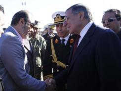 Defense Secretary Leon Panetta greets members of the Libyan delegation on the tarmac during his arrival in Tripoli.