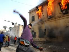 An Egyptian protester throws a stone toward soldiers, unseen, as a building burns Saturday during clashes near Tahrir Square, in Cairo.