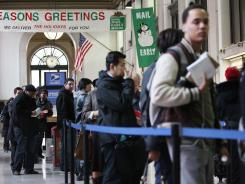 People wait for mail services at a post office in New York City. The postal service expects to handle about 1 billion fewer holiday cards, letters and packages this year, compared to last year.