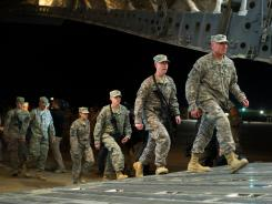 US soldiers board the last C17 aircraft carrying U.S. troops out of Iraq at Camp Adder on the outskirts of Nasiriyah.