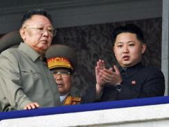 North Korea leader Kim Jong Il, left, walks by his son Kim Jong Un as they attend a massive military parade Oct. 10, 2010.