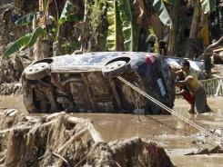 Residents retrieve a car Monday that was washed away in Friday's flash flooding in Iligan city in the southern Philippines.