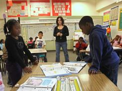 First graders read out loud from their work book as teacher Lori Peck looks on at Grace L. Patterson Elementary school in Vallejo, Calif., last year.