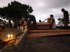Soldiers carry coffins of flash flood victims during a mass burial Tuesday at a cemetery in Iligan.