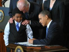 President Obama signs the health care overhaul bill into law on March 23, 2010. Marcelas Owens of Seattle and Vice President Biden look on. Republicans said the law would kill jobs.