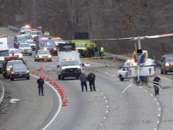 A State Police helicopter lands on the southbound lanes of route 287 in Harding Township, N.J., where a small plane headed for Georgia crashed, raining debris down on the highway and local streets.