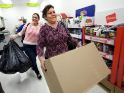 Yoneira Noriega, left, and her mother, Anna Noriega, leave the Kmart layaway department with gifts.