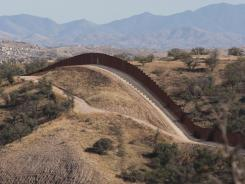 This photo shows the border fence stretching west of Nogales, Ariz., into the Coronado National Forest. The Defense Department said Tuesday it will reduce National Guard troop levels along the border.