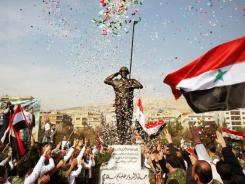 Pro-regime demonstrators at a statue of a solider during a rally at Umayyad Square in Damascus, Syria.