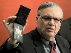 Maricopa County Sheriff Joe Arpaio shows his badge as he holds a ceremony Wednesday where 92 of his immigration jail officers, who lost their federal power to check whether inmates are in the county illegally, turn in their credentials.