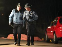 Kansas State Troopers pass near the covered body of a suspected shooter who shot and killed Sgt. David Enzbrenner on Dec. 9.