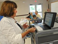 Pat Morales puts her primary election ballot in a new voting machine at the Western Turnpike Rescue Squad polling place in Guilderland, N.Y., on Sept. 14, 2010.